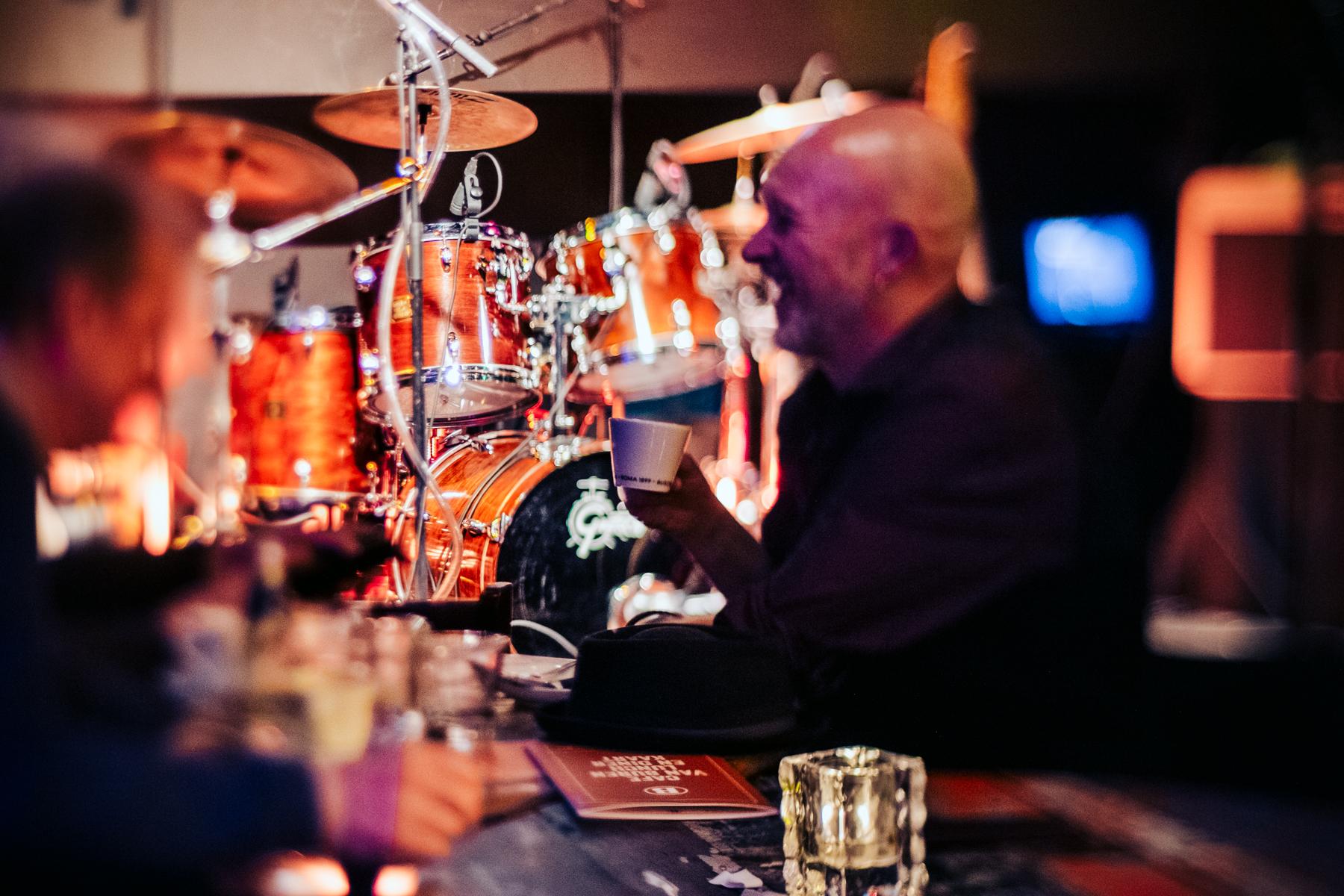Man drinkt koffie met drumstel op de achtergrond bij Café Van Buren